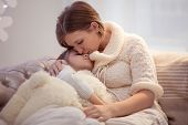 The Girl Got Sick. Mom Hugs And Kisses A Sick Daughter poster