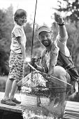 Black and white photo of Smiling father and son catching fish on pier poster
