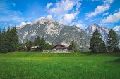Old Traditional Farmhouse On Top Of A Hill In Scenic Wonderland Scenery In The Alps. poster