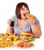 stock photo of high calorie foods  - Overweight woman eating fast food - JPG