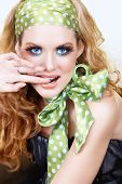 foto of hair bow  - Beautiful young woman with retro green polka dot head band and bow scarf biting her finger with a smile long feather lashes - JPG