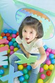 Little Smiling Girl Playing Lying In Ball Park. Girl Learning The Letters. poster