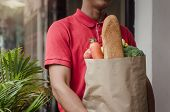 Smart Food Delivery Service Man In Red Uniform Holding Fresh Food Set Bag Waiting For Customer At Th poster