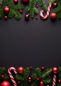 Black Christmas and New Year background. Decorative border of fir branches, Christmas balls and Cand poster