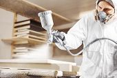 Man Working With Paint Spray Gun, Airless Spraying To Wood poster