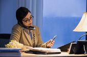 Hispanic businesswoman using telephone and cell phone
