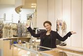 stock photo of flogging  - Mixed Race woman working in boutique - JPG