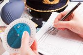 Close up of an airplane pilot hand with holding pattern calculator filling in an flight plan and wit