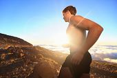 Runner athlete running. Sport man jogging outdoor in sunshine at sunset in scenic nature. Fit muscular male fitness guy training trail running for marathon run. Sporty fit athletic man working out.
