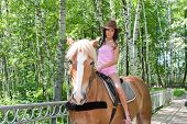 A Young Beautiful Woman Sits Astride On A Horse