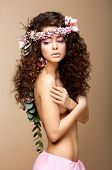 Sultry Beauty. Attractive Naked Woman With Long Curly Hair And Wreath Of Flowers
