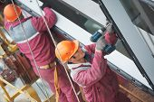 Two builders worker installing glass windows on facade of business building