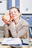 Senior business woman with piggy bank in her office at the desk
