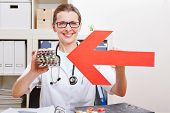 Happy female doctor pointing red arrow to medical pills in her office