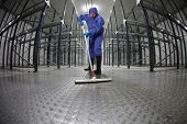 worker in protective uniform cleaning floor in empty storehouse - fish-eye lens