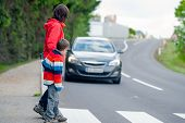 stock photo of pedestrian crossing  - Mother and son passing a street when a car coming - JPG