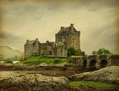 Eilean Donan castle on a cloudy day. low tide. Scotland, UK. Photo in retro style. Paper texture.