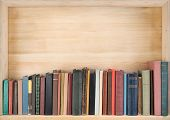 stock photo of spine  - Old books on a wooden shelf - JPG