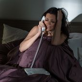 Crying young woman calling phone in bed