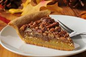 stock photo of pecan  - A slice of pecan pie on a colorful holiday table - JPG