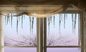 stock photo of icicle  - Icicles on blue pink and and purple sky viewed through old window with ice crystals - JPG
