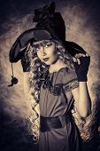 Black-and-white portrait of a beautiful little girl in a costume of witch. Vintage style.