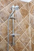Silver shower head with running water in a bathroom