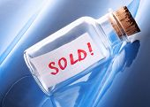 """An artistic sales concept of a vintage bottle with a message """"Sold!"""""""