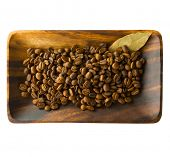 Coffee beans on a acacia wood tray,with bay leaf?(laurel) , Isolated on white.