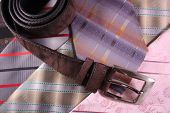 Multicoloured neckties and leather strap