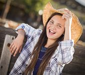 stock photo of preteen  - Preteen Girl Wearing Cowboy Hat Portrait at the Pumpkin Patch in a Rustic Setting - JPG