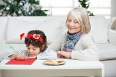 Grandmother looking at boy writing letter to Santa Claus during Christmas at home