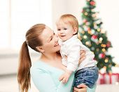 christmas, x-mas, winter, family, people, happiness concept - happy mother with adorable baby