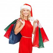 shopping, sale, gifts, christmas, x-mas concept - smiling woman in red dress and santa helper hat wi