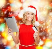 christmas, x-mas, online shopping concept - woman in santa helper hat with tablet pc computer and credit card