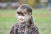 image of overcoats  - Little cute girl in overcoat looks at distance at autumn day - JPG