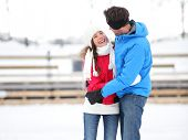 Ice skating romantic couple on date iceskating embracing. Young couple holding hands on ice skates o