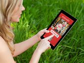 Girl Holds A Tablet On A Background Of Green Grass And Makes Online Shopping
