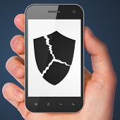 Security concept: Broken Shield on smartphone