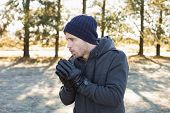 picture of shivering  - Young man in warm clothing shivering while having a walk in forest on a winter day - JPG