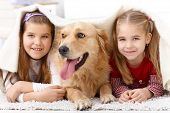 Little sisters lying on floor with dog, having fun under blanket, smiling.