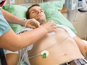 Cropped image of nurse sticking holter on patient's chest in hospital