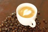 pic of piccolo  - A delicious piccolo latte in a small white cup with a heart shaped coffee art design sitting on a wooden table surrounded by roasted coffee beans - JPG