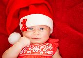 Closeup portrait of cute newborn girl wearing Santa hat, lying down on red background, Christmas hol