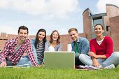 Group portrait of young students with laptop in the lawn against college building