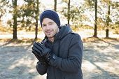 Portrait of a smiling young man in warm clothing shivering while having a walk in forest on a winter