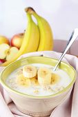 Tasty oatmeal with bananas and milk on table on bright background