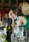 Happy smiling woman sitting at a bar counter