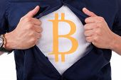image of bitcoin  - Young businessman opening his shirt and showing bitcoin currency symbol - JPG