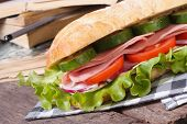Ciabatta With Ham And Vegetables On A Background Of Books